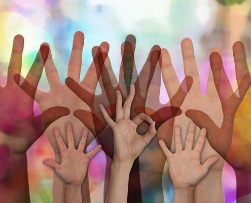 Helfende Hände vor einem bunten Hintergrund